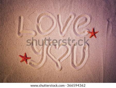 love you text written on sand of sea beach - stock photo