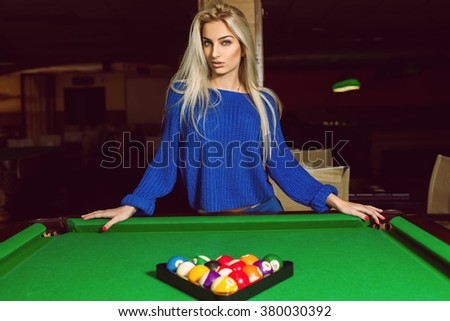 Lovely adult blonde posing near a billiard table with a pyramid of balls. Billiard sport concept. Pool billiard game. American pool billiard. - stock photo