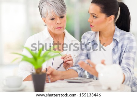 lovely adult daughter helping worried senior mother with her finances - stock photo