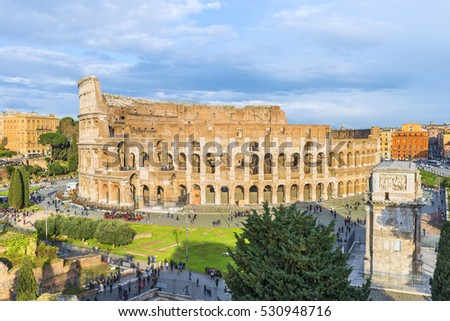Lovely aerial panoramnic view on the Great Roman Colosseum ( Coliseum, Colosseo ,also known as Flavian Amphitheatre ) at sunset. Famous world landmark. Scenic urban landscape. Rome. Italy. Europe