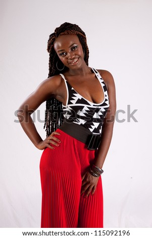 Lovely African American black woman in red slacks, looking at the camera with a friendly but serious expression with her hands on her thighs - stock photo