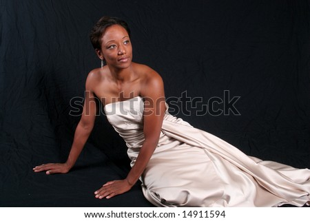 Lovely African American woman reclining in a formal, white dress - stock photo