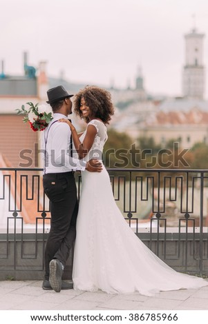 Lovely african newlyweds softly holding each other and smilling. Rooftop. Ancient Lviv architecture on background - stock photo