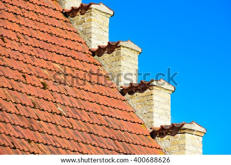 Lovely architectural detail of an old brick house where the yellow facade meets the red tiled roof.  - stock photo