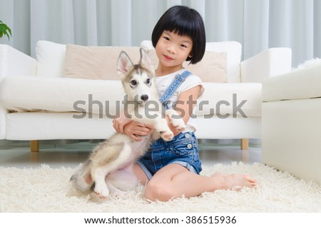Lovely asian girl playing with dog in the living room - stock photo
