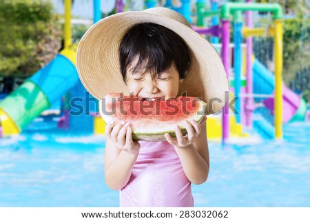 Lovely asian little girl wearing a big hat and swimwear at pool while eating a watermelon - stock photo