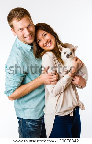 Lovely attractive couple and dog together, studio shot, white background