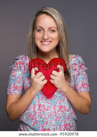 Lovely attractive girl with heart in hands over grey background - stock photo