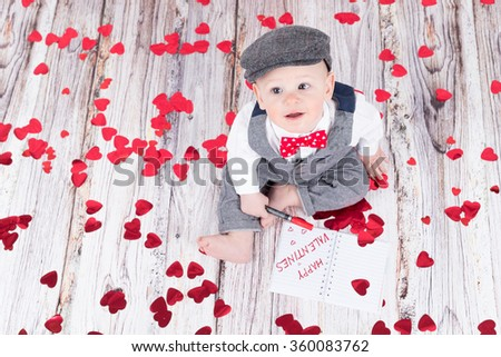 lovely baby boy in barret sitting and wishing happy valentines - stock photo