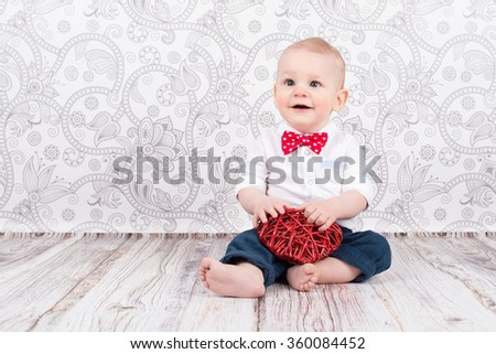 Lovely baby boy smiling and  playing with red wattled heart