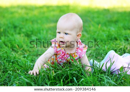 Lovely baby girl happy  in fashion dress outdoor on the green lawn at the warm day