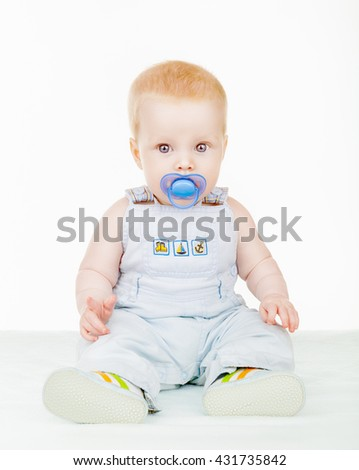 Lovely baby sitting on the floor with a pacifier isolated on white background - stock photo