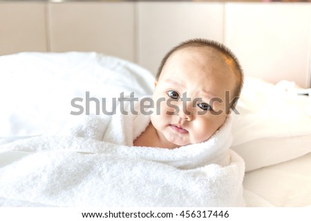 lovely baby with white towel on bed