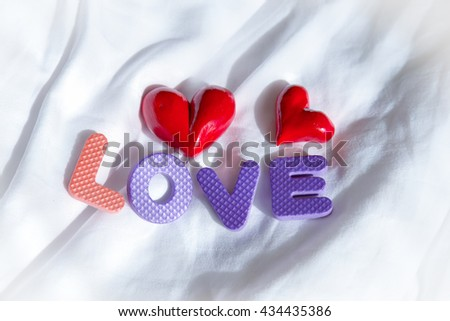 Lovely background with love words and cute red heart on white fabric bed. - stock photo