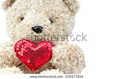 lovely bear doll holding red heart shape over white background - stock photo