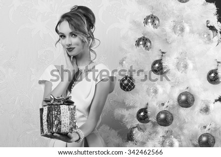 lovely black and white fashion woman with elegant style, pearl necklace, stylish make-up and hair-style posing near christmas tree in indoor shoot with gift box in the hand  - stock photo