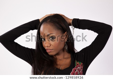 Lovely black woman in a black blouse with roses, standing with her hands behind her head and looking friendly with a sexy expression at the camera