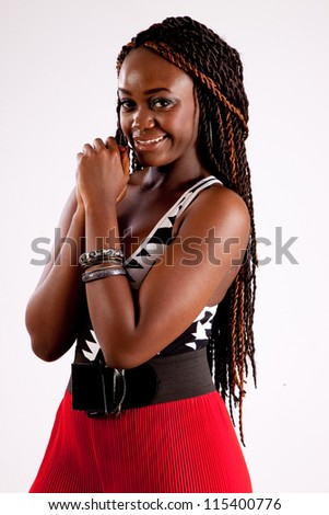 Lovely black woman in red pants,  looking at the camera with a friendly, coy expression - stock photo