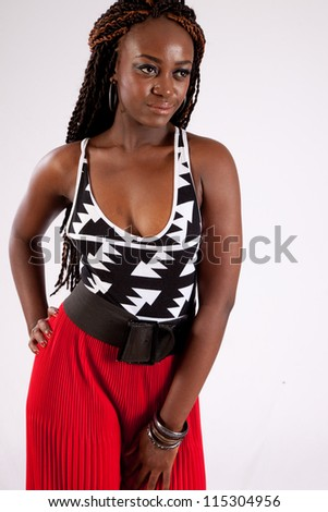 Lovely black woman standing in red slacks with a thoughtful and friendly expression on her face  and her hand on her hip - stock photo