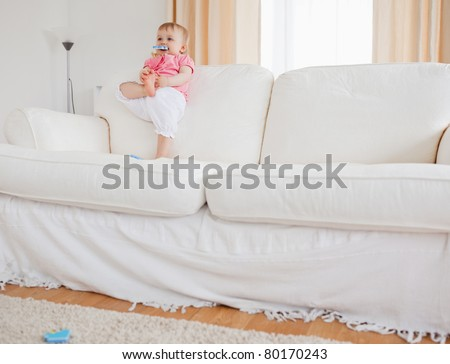 Lovely blond baby playing with puzzle pieces while standing on a sofa in the living room - stock photo