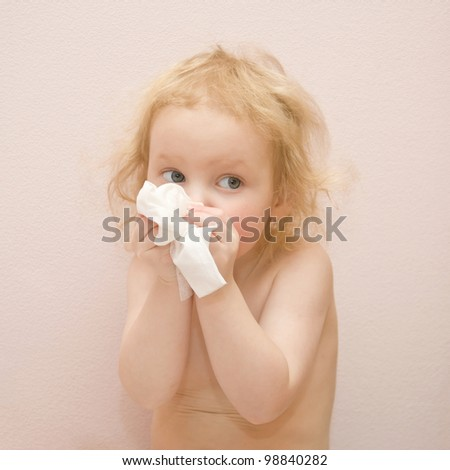 Lovely blond curly-haired baby girl with blue eyes is sick. She has a runny nose. Blowing his nose with disposable tissues. Isolated on pink background - stock photo