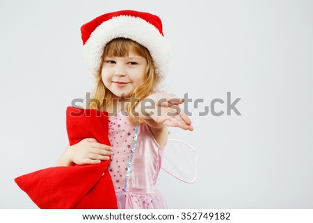 Lovely blond girl, with curly hair, wearing on pink dress, red santa hat and fairy wings, holding red bag for presents and showing something, on white background, in studio, waist up