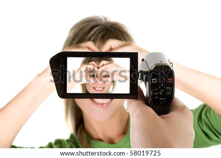 Lovely blond girl with hands as heart at camcorder - stock photo