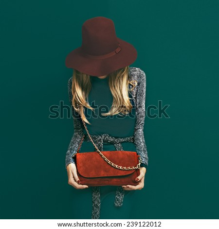Lovely Blond Model in fashionable red Hat and a red Clutch on green background - stock photo