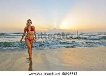 lovely blonde bikini model walks from atlantic ocean at beach at dawn