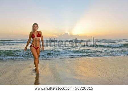 lovely blonde bikini model walks from atlantic ocean at beach at dawn - stock photo