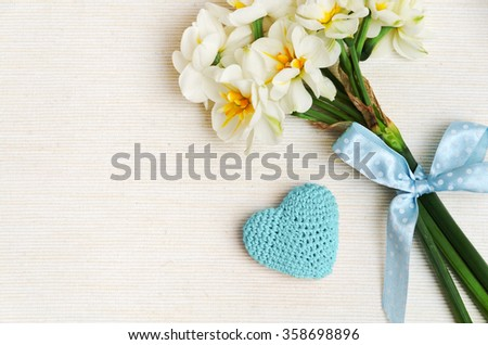 lovely bouquet of narcissus with a charming blue bow and knitting heart on beige cotton - stock photo