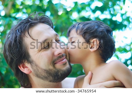 Lovely boy and his father holding him in hands in nature - stock photo