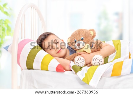 Lovely boy sleeping with a teddy bear in a comfortable bed covered with a striped multicolored blanket at home - stock photo