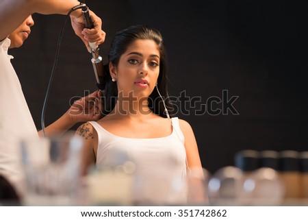 Lovely brunette having her hair curled in beauty salon - stock photo