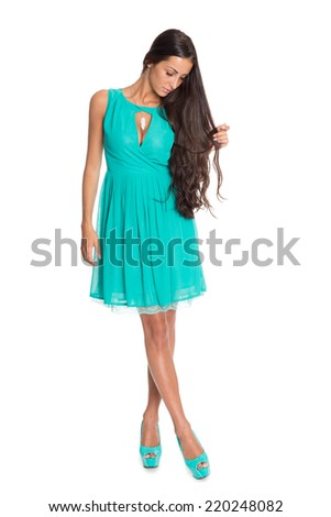 Lovely brunette in a turquoise dress isolated on white.