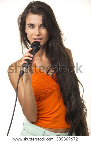 Lovely brunette with long hair is holding microphone on the white background. Beauteous woman in orange shirt with microphone.