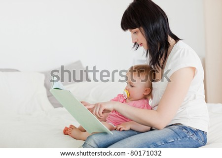 Lovely brunette woman showing a book to her baby while sitting on a bed in her apartment