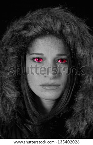 Lovely Caucasian woman in a heavy winter coat with a fur lined hood over her head, looking at the camera with demonic red eyes