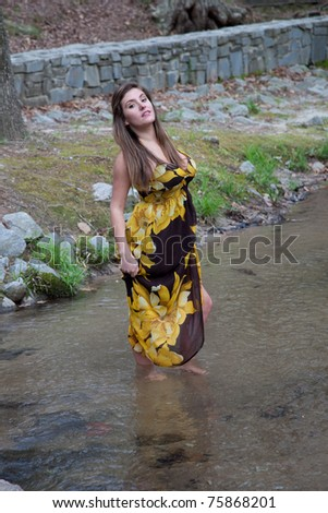 Lovely caucasian woman in yellow dress standing in a stream with pleasing eye contact