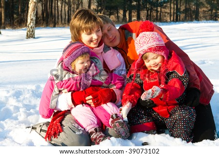 Lovely cheerful family having fun in the winter park - stock photo
