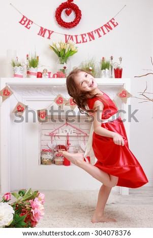 Lovely cheerful little girl in a red dress dancing and laughing - stock photo