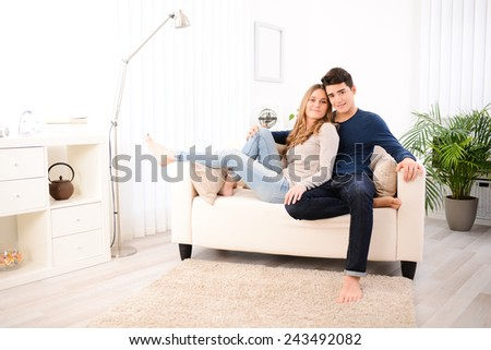 lovely cheerful young couple man and woman happy together on sofa at home