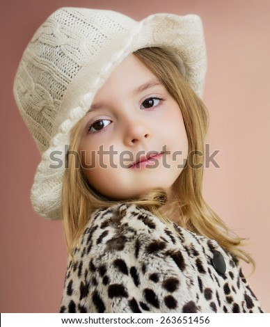 Lovely child girl portrait. Young model posing in hat and fur coat.Fashion kid closeup. - stock photo