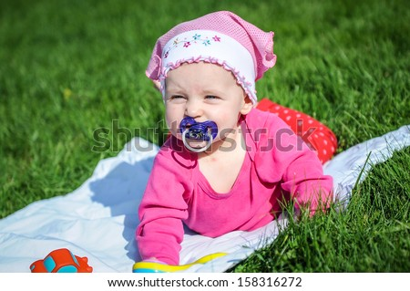Lovely child playing on grass  - stock photo