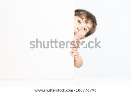 Lovely child trying to scare behind white wall - stock photo