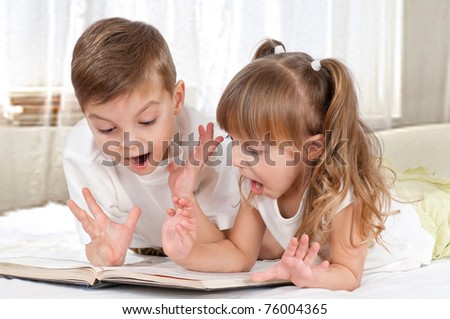 Lovely children - brother and sister, reading a book, on the bed - stock photo