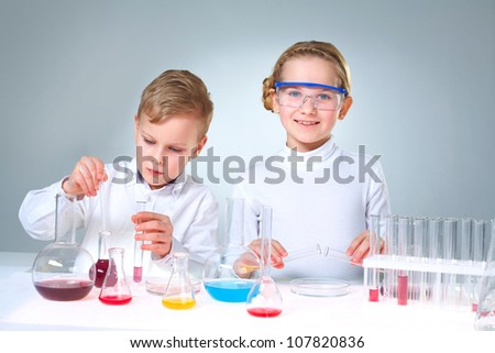 Lovely children doing homework experimenting with substances and samples - stock photo