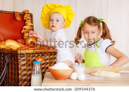 lovely children knead the dough in the kitchen - stock photo
