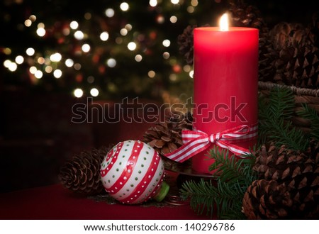 Lovely Christmas Still Life of a Lit Red Candle with an Ornament and Pine Cones with a Christmas Tree in the Background and Room for your Words or Text. - stock photo