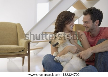Lovely couple and dog at home - stock photo